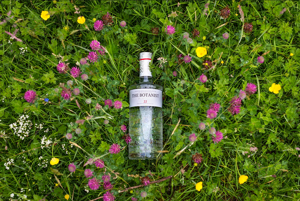 A bottle of The Botanist gin laid on top of a selection of botanicals