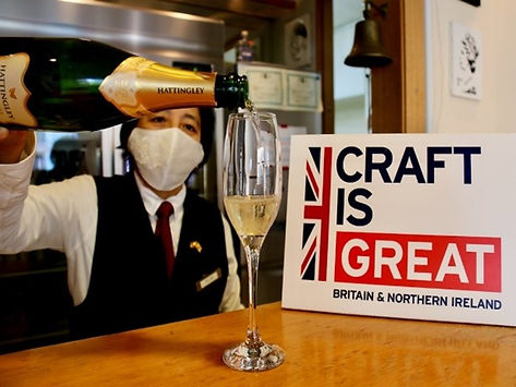 Man with the mask pouring champagne into the glass next to the Craft is GREAT sign