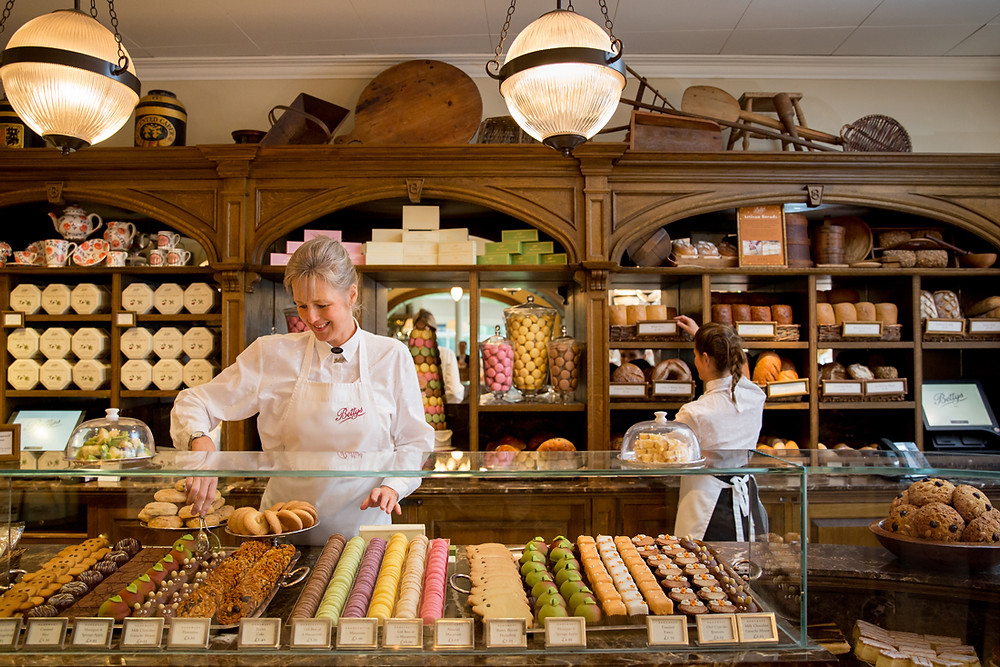 Woman stands by the display of cakes and biscuits
