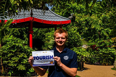 Man stood outside holding a piece of paper which says Tourism