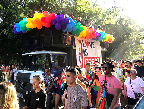 Attendees at a Pride parade, featuring a bus decorated with Love is Great branding and rainbow-coloured balloons