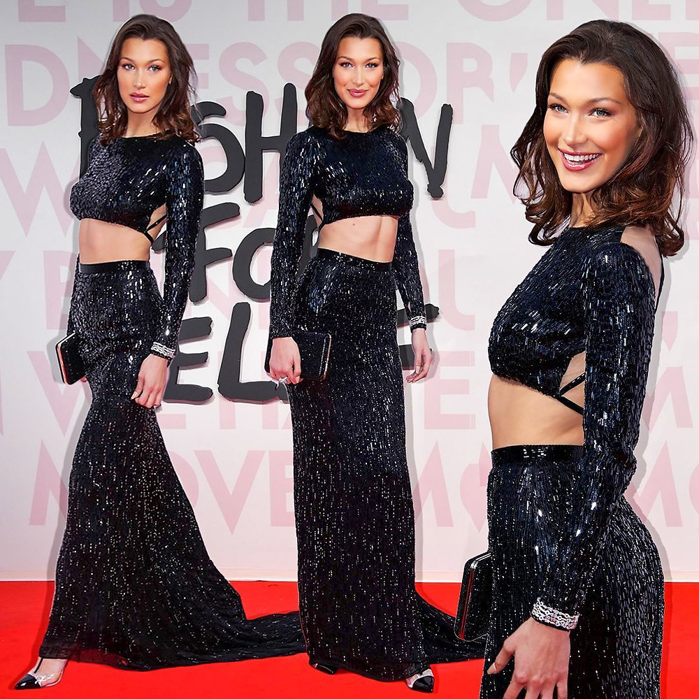 A woman dressed in a black sparkly cropped top and long skirt.