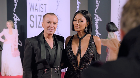 Julien MacDonald and a mona posing on a red carpet
