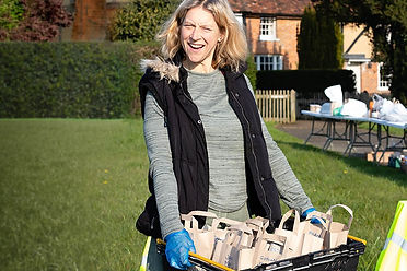 Woman carrying a crate containing paper bags