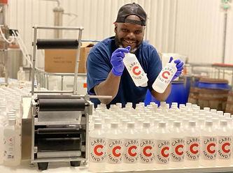 Man holding up bottles of hand sanitizer