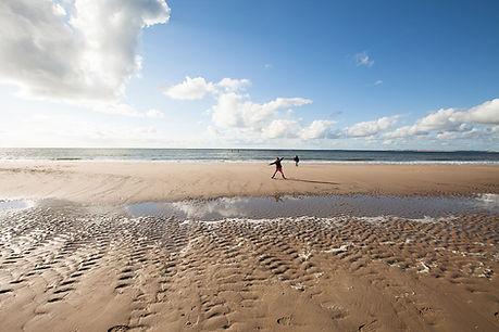 Strand, zee, kust van Zeeuws-Vlaanderen met spelende kinderen