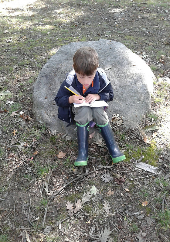 Child writing in nature