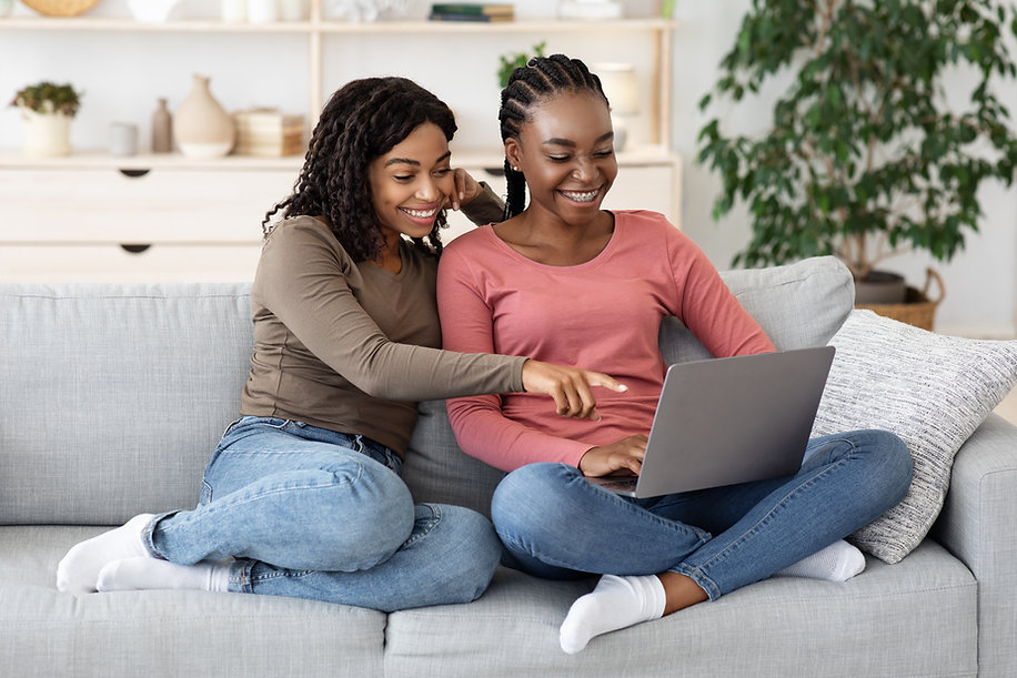 two-smiling-black-women-using-laptop-at-
