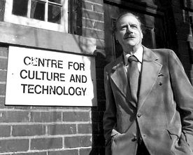 Marshall McLuhan outside the historic Coach House with the sign: Centre for Culture and Technology