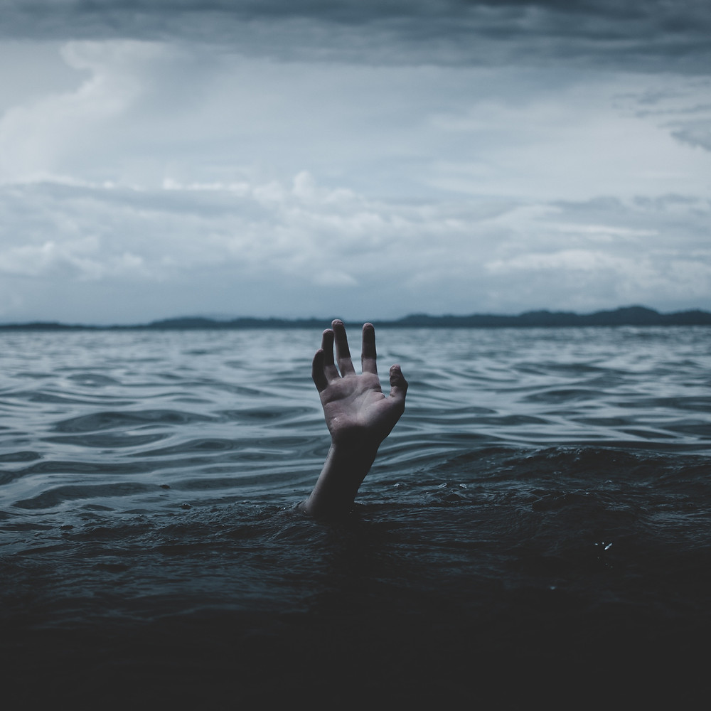 A single hand reaches out of a large body of dark water, asking for one last chance for rescue.