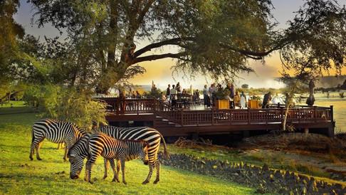 O pôr do sol, as Cataratas ao fundo e o rio Zambezi vistos do deck do Hotel Anantara Royal Livingstone.