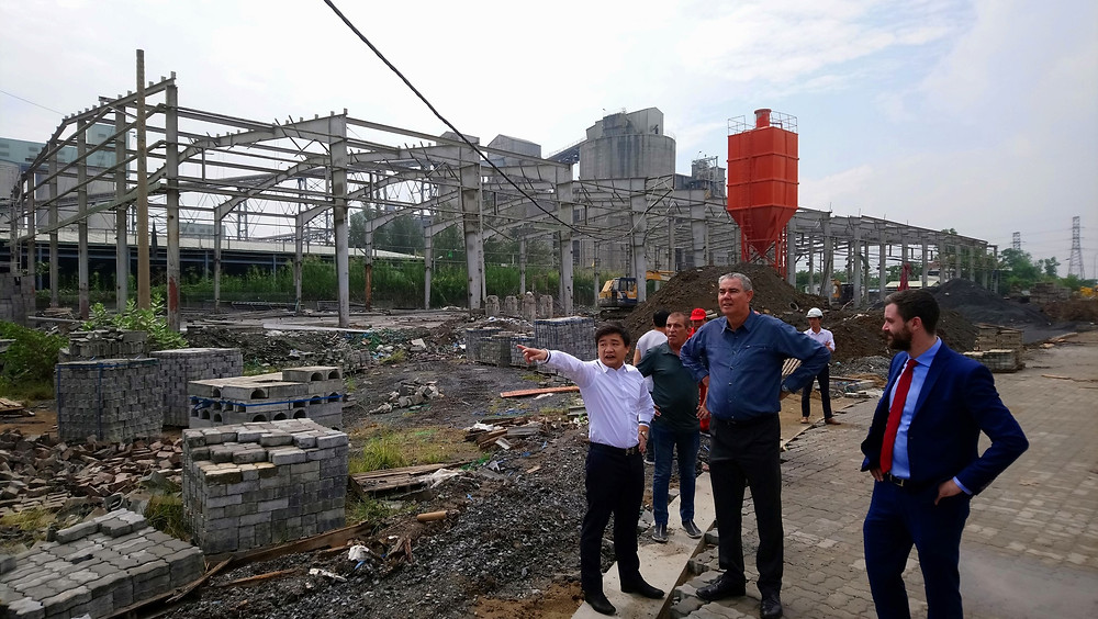 Mr Minh (UniDepot) speaks with Paul Koch (Triac Composites) after the signing ceremony for the new factory which is being totally refurbished (see behind). John Campbell (Savills) listens in.