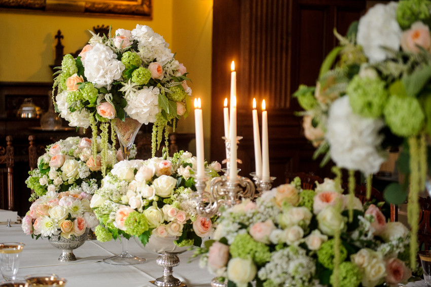 These opulent and lush table arrangements are set on the Strathmore dining table at Glamis Castle made in a tall Martini glass vase and large and small silver vintage bowls filled beautiful textures of white Hyydrangea heads, Ameranthus green trails, pearl David Austin Roses, white Avalanche roses, cream spray roses white lilac, green Viburnum Snowball, white Stock, cream Astilbe with Salal and Eucalyptus.