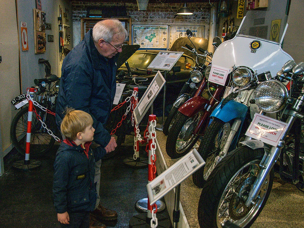 Grandfather and grandson view vintage motorcycles at Dundee Museum of Transport