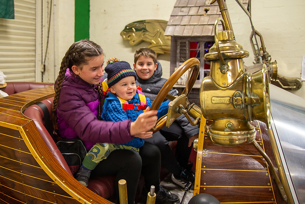 Three children with a replica of Chitty Chitty Bang Bang at Dundee Museum of Transport