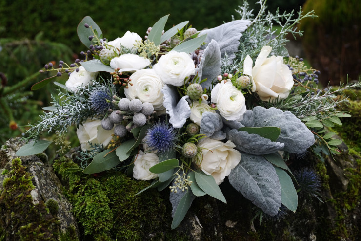 A white and grey bouquet of white rose, white ranunculus, thistle with selection of beautiful seasonal winter foliage.