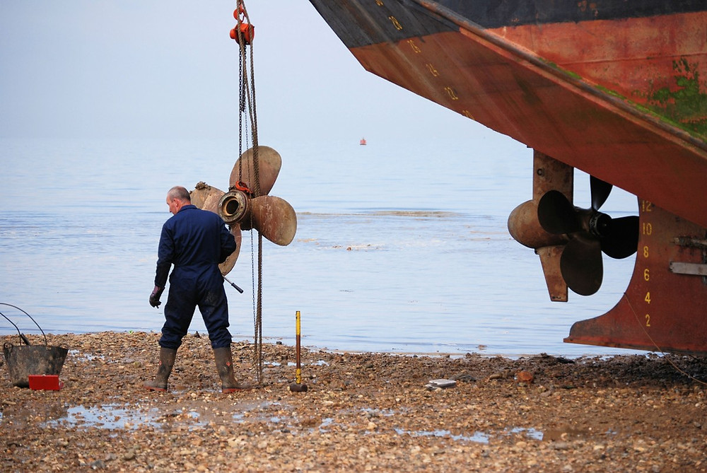 Homme démontant une hélice d'un moteur de bateau