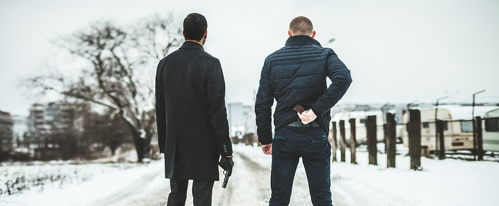 two men in snow with guns