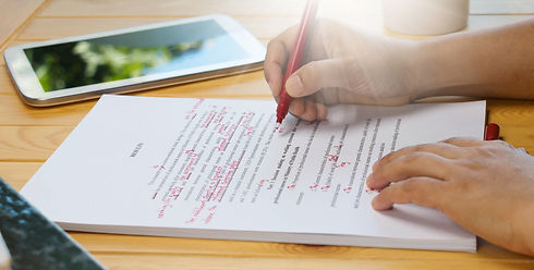 hand holding red pen over proofreading t
