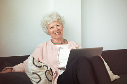 happy-senior-woman-sitting-on-the-couch-