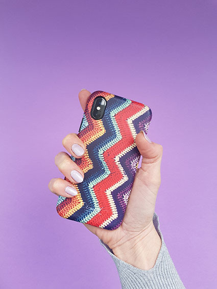 Hand holding phone with Decouart crochet print case