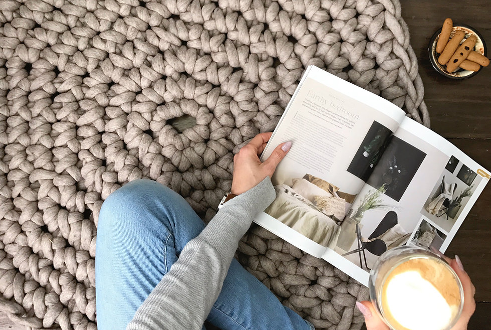 Reading magazine on round floor rug made of chunky grey yarn