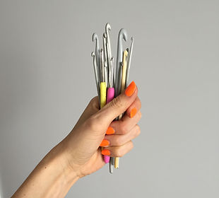 Crochet hooks held in hand with bright manicure nails