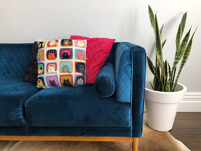 Three cushions on a velvet blue couch against a white wall. The cushion in front is made of colourful crochet squares of cats.