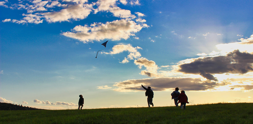 four kids flying a kite, running on a green hill with an amazing sky scenery