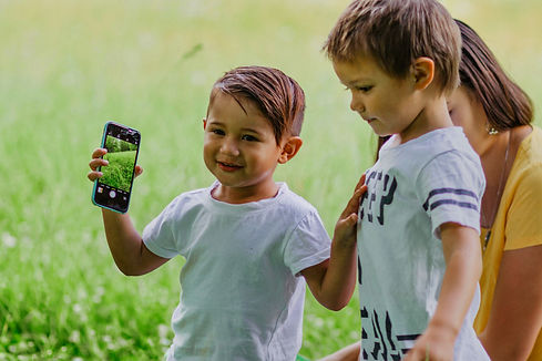 two small boys standing together smiling and holding a phone up