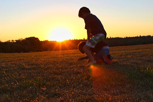 2 young boys playing on grass, one sitting on the others back with a gorgeous sunset in the background.