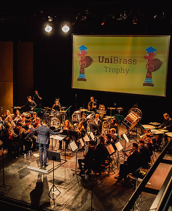 Photo of brass band performing in Theatr Bryn Terfel at a UniBrass contest hosted at Bangor University. Background of 2019 UniBrass Contest logo