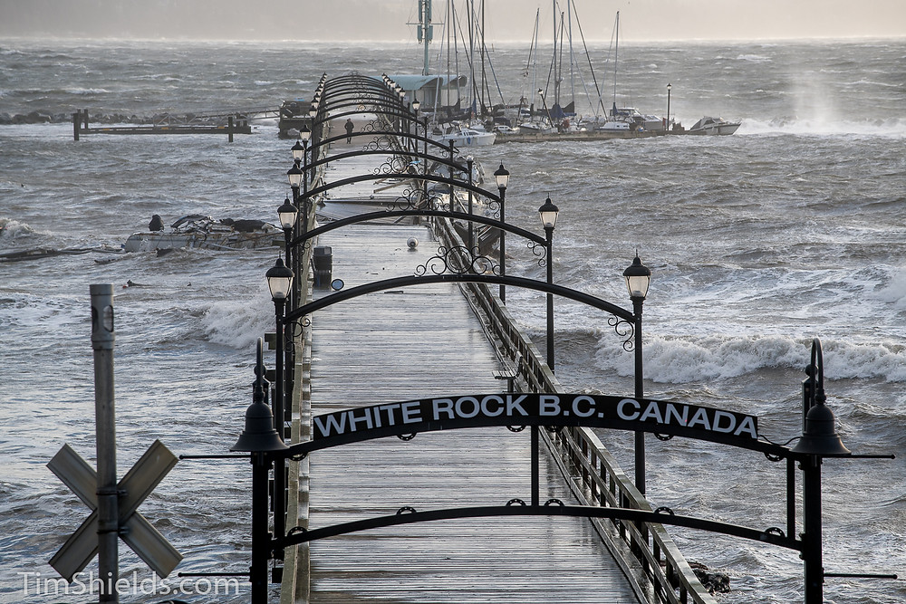 White Rock pier cut in half.  one man stands alone.