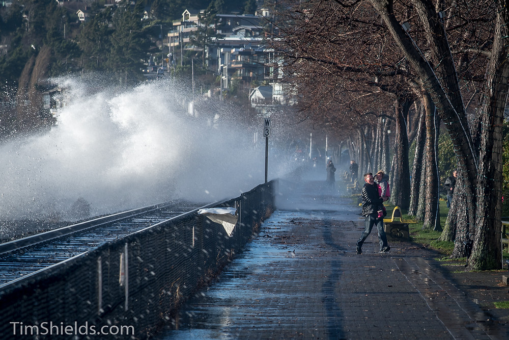 man runs from wave in White Rock, BC, Canada