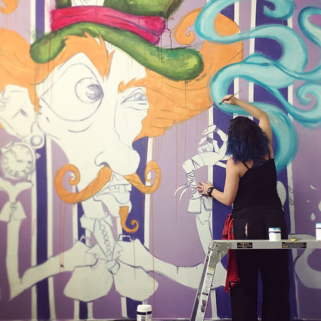 Tankateo painting a Mad Hatter mural in Perth