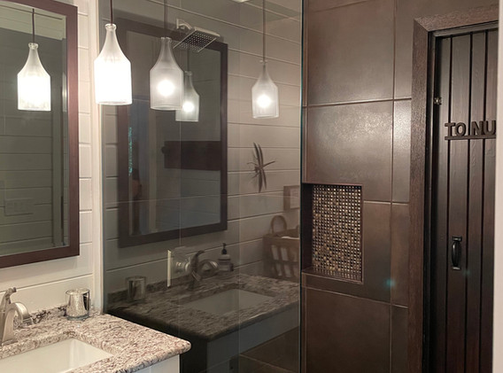 Tiled shower with glass door, and built-in shampoo niche