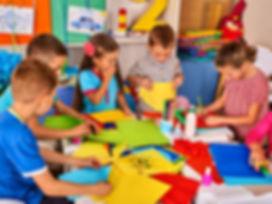 Child cutting paper in class. Kids development and social lerning children in school. Children's pro
