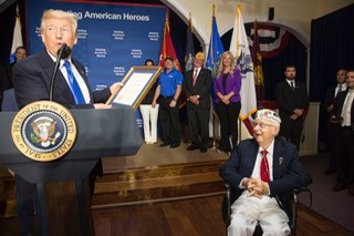 President Donald J. Trump presents Veteran Bob Bishop with a certificate of recognition at the Salute to American Heros at AMVETS Post 44, Tuesday, July 25, 2017, in Struthers, Ohio. (Official White House Photo by Shealah Craighead)