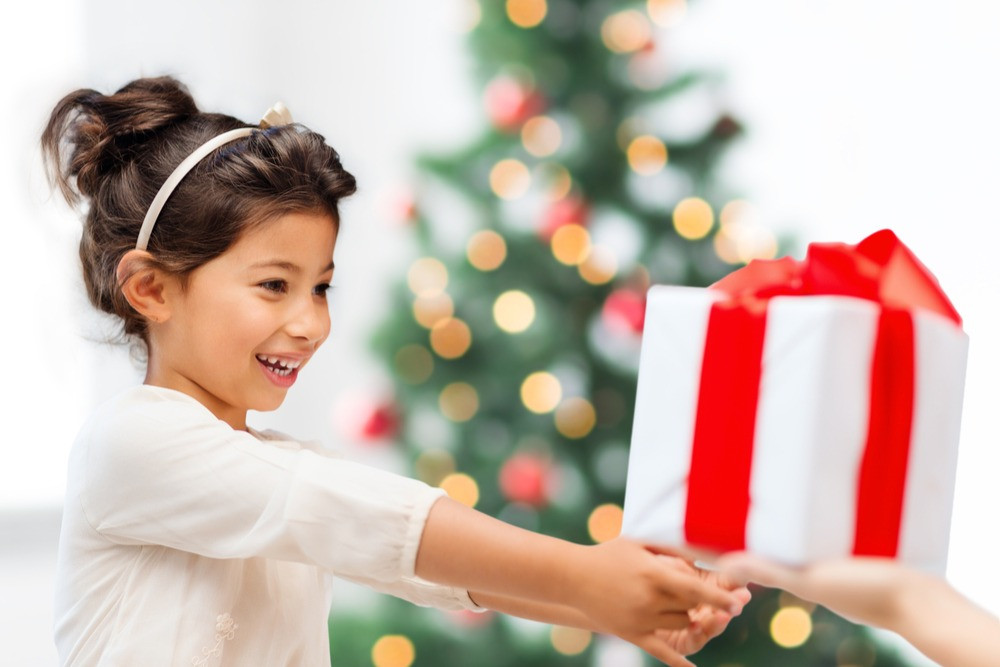 Cute kid giving present under the christmas tree