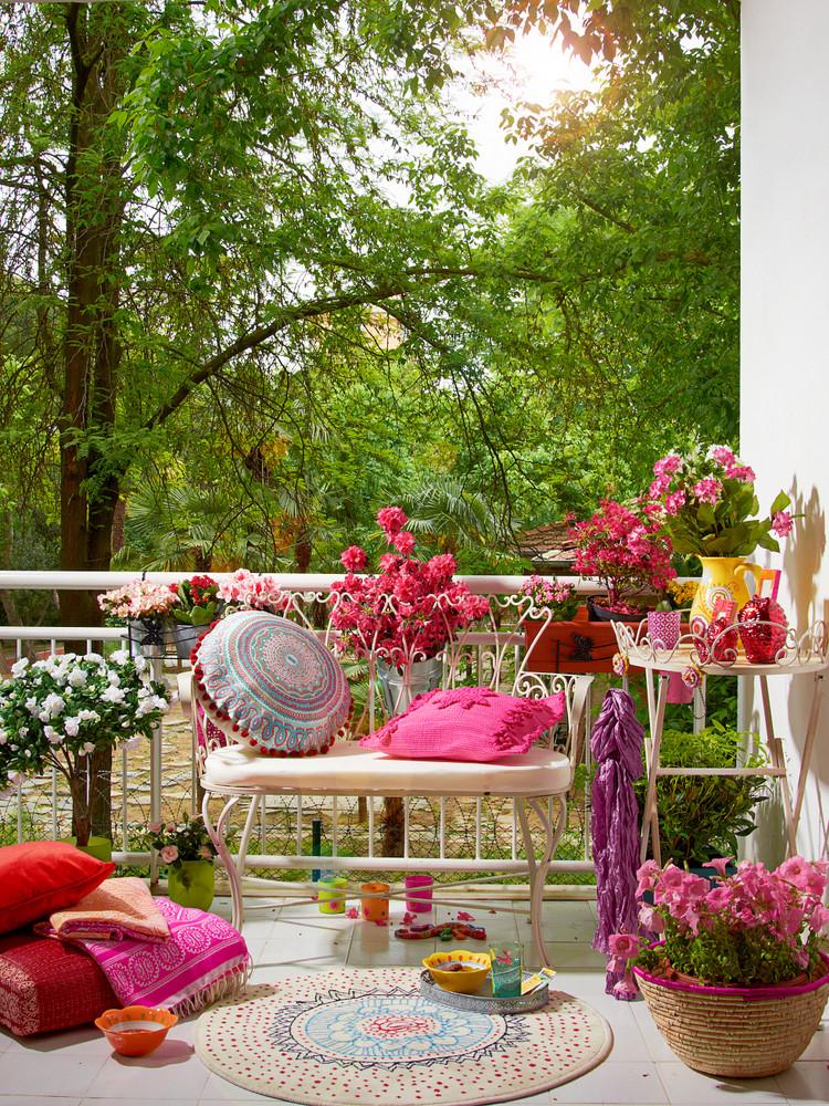 Balkon met roze bloemen en gezellig zitje
