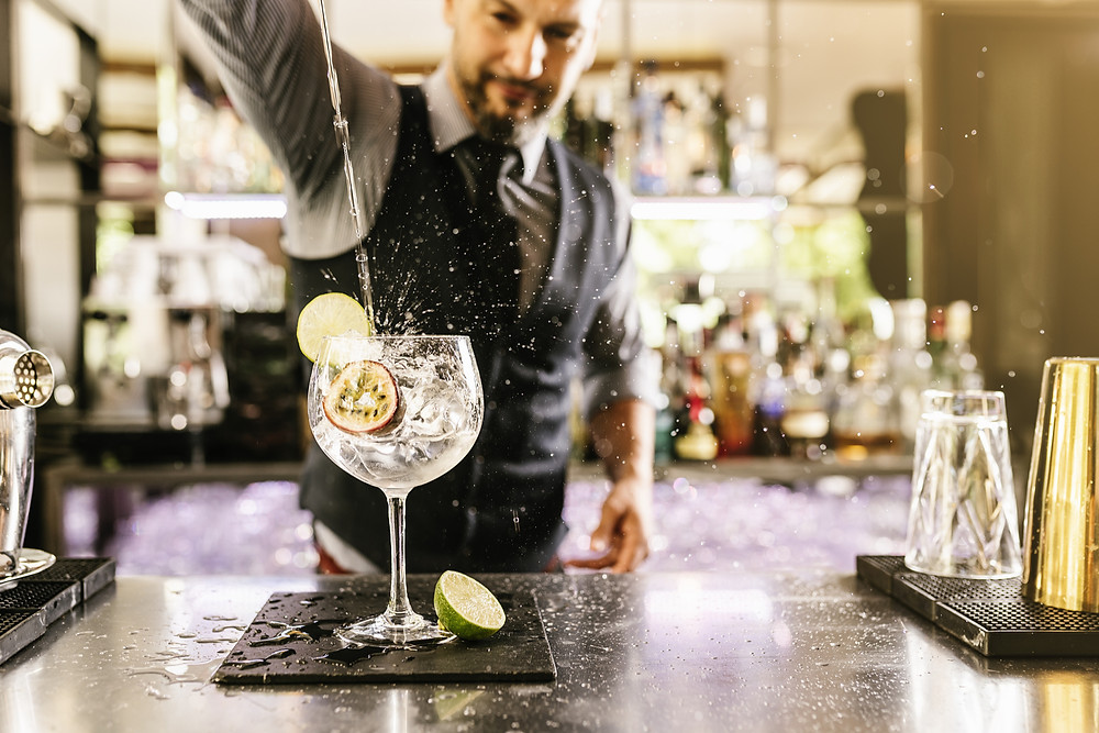 Bartender pouring tonic in a gin glass