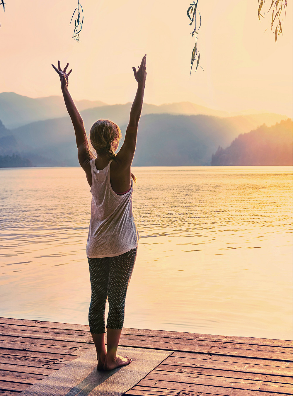 Beautiful young woman doing sunset yoga at the lake