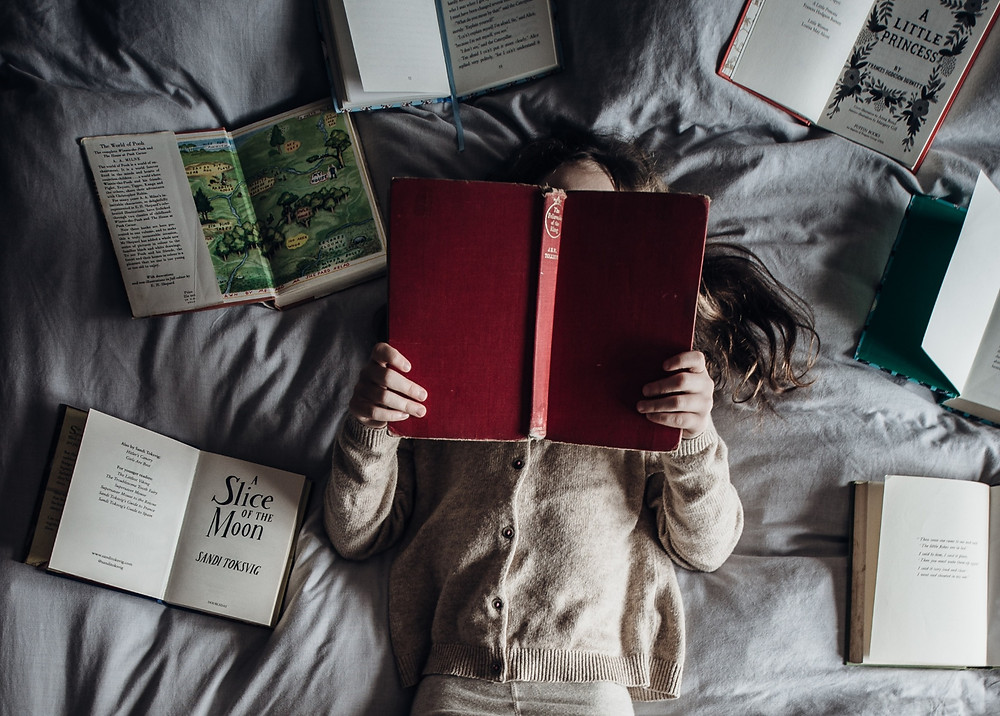 girl in bed with books