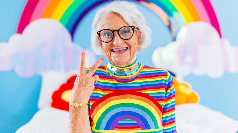Older-lady-making-v-sign-with-rainbow-shirt-and-rainbow-clouds-on-background