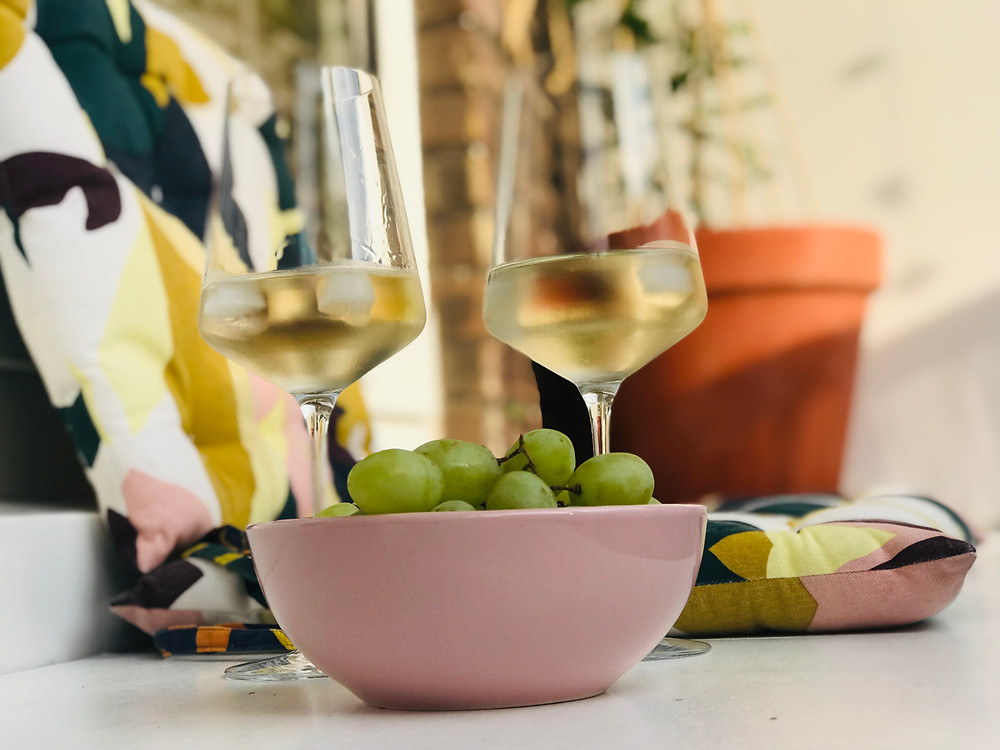 Two-glasses-of-chilled-white-wine-and-bowl-of-grapes-on-balcony