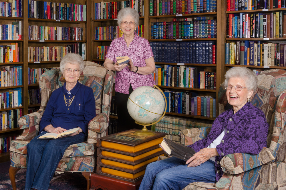 Old ladies reading books in cosy library