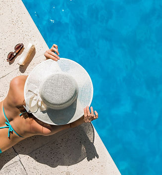 woman-in-wide-brimmed-hat-lying-on-pool-