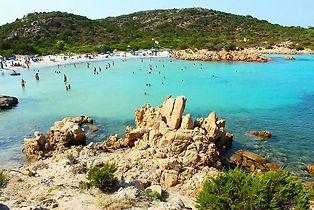 Caratterizzata da un ampio arco di sabbia bianca finissima circondato da una ricca macchia mediterranea, separata in due da un promontorio di particolari rocce rosa