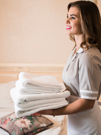 smiling-young-chambermaid-with-stack-of-