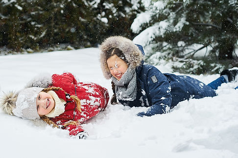cute-children-playing-in-snow-outdoor-near-the-christmas-trees.jpg